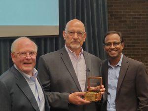 Greg Taucher holding the Hopp Faculty Fellow Award, next to Tony Hopp and Dean Prabu David