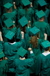 People in green graduation caps and gowns