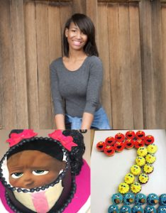 Young woman standing against wall smiling with picture of a cake shaped like girl face and picture of a number two made out of cupcakes that look like Seasame Street characters.