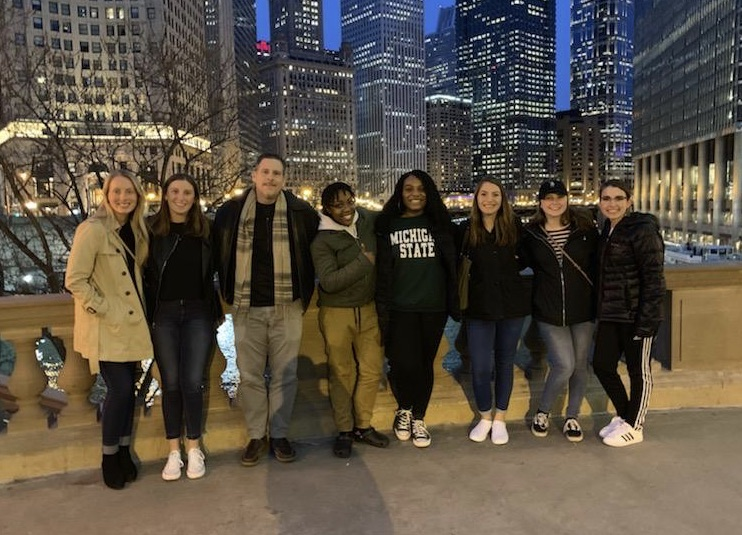 Group of college students and Professor Epps smiling with the city of Chicago in the background.