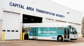 "A picture of a bus outside a transportation warehouse. The bus is wrapped with ""Be Counted"" against a blue background."