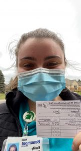 Masked woman holding inoculation card.